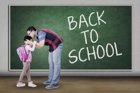 niños saliendo de la escuela: Concepto de nuevo a la escuela con un joven padre besar a su hija en el aula antes de estudiar Foto de archivo
