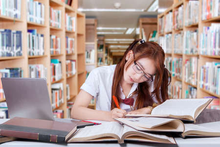 nerd girl: Portrait of cute female high school student studying in the library with laptop and write on the book at desk