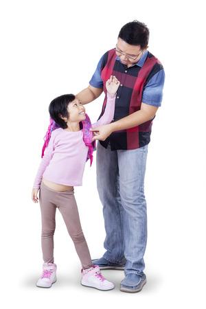 niños saliendo de la escuela: Retrato de joven padre ayuda a su hijo a prepararse antes de ir a la escuela, aislada en el fondo blanco Foto de archivo