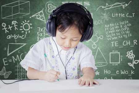 person writing: Female kindergarten school student studying in the classroom while wearing headphones and write on the paper Stock Photo