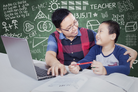 learning computer: Portrait of male elementary school student studying in the class with his teacher while talking and discussing Stock Photo