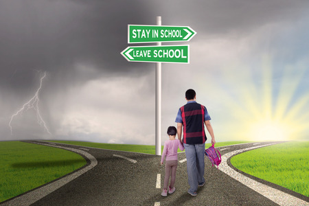 young leave: Rear view of father and his daughter walking on the road with road sign to stay or leave school Stock Photo