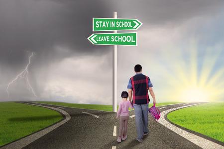 niños sosteniendo un cartel: Vista trasera de padre y su hija que recorren en el camino con la muestra de camino para permanecer o salir de la escuela Foto de archivo
