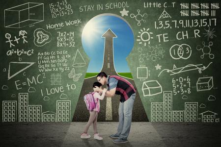 niños saliendo de la escuela: Padre joven besa a su hija antes de ir a la escuela en frente de un ojo de la cerradura con garabatos y la flecha hacia arriba