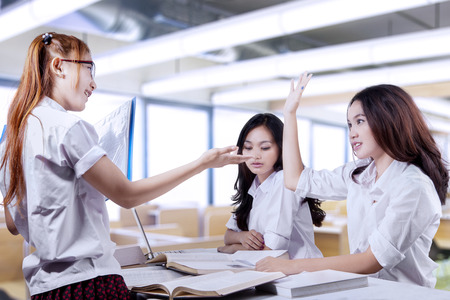 talking: Attractive female students doing schoo task together with one of the student inquire a question Stock Photo