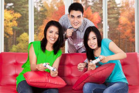 fille indienne: Groupe de jeunes asiatiques profiter des vacances d'automne en jouant à des jeux vidéo ensemble à la maison