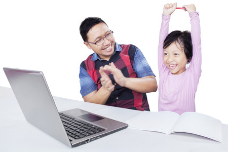 successful man: Cheerful little girl raising hands with her dad giving applause after finishing her study with laptop, isolated on white
