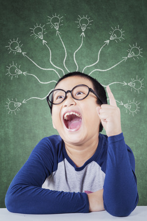 branchy: Image of a creative student with branchy light bulb and wearing glasses in the classroom Stock Photo