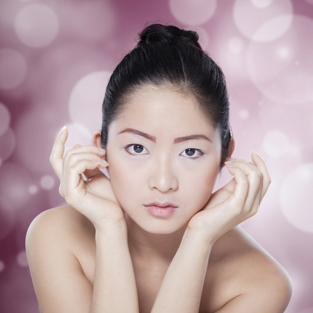 healthy looking: Portrait of young chinese model with healthy skin and elegant face, looking at the camera on blur background