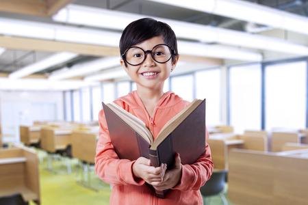 colegiala: Retrato de la hermosa ni�a sonriente en la c�mara, mientras que la lectura de un libro en el sal�n de clases