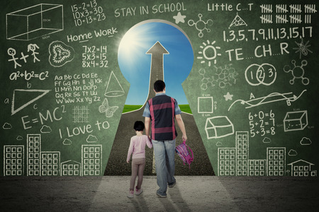 Rear view of little girl and her dad walking through a keyhole with doodles and upward arrow Banque d'images