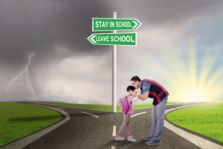 young leave: Portrait of young father kissing his daughter on the road with road sign to stay or leave school