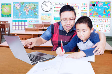 kids laptop: Portrait of young male teacher helps his student to study with laptop in the classroom Stock Photo