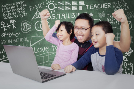 asia children: Two attractive students and their teacher celebrate success by raising hands together while looking at the laptop computer in the classroom