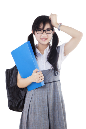 Image of a frustrated high school student standing in the studio while carrying bag and holding folder, isolated on white background