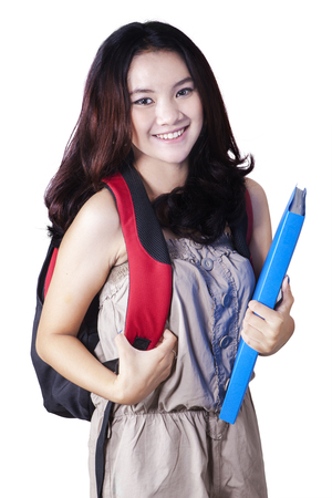 holding back: Photo of a beautiful high school student standing in the studio while carrying backpack and smiling at the camera, isolated on white background