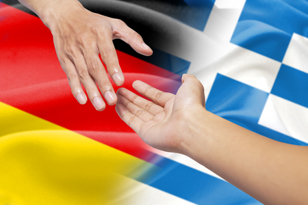 rescuing: Hand giving a help and pulling a persons hand for rescuing in front of the german and greece flags