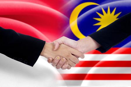 buen trato: Dos empresarios de agitar las manos después de mucho frente a las banderas de Indonesia y Malasia Foto de archivo