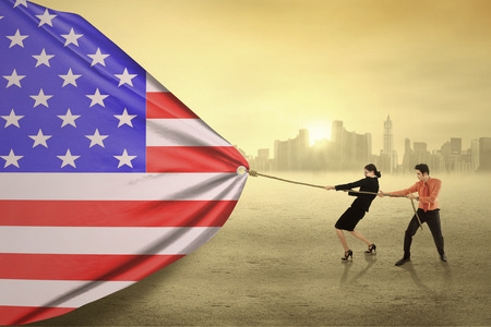 asian american: Two young entrepreneur try to pull a big american flag, shot outdoors