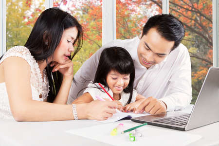 family asia: Photo of attractive little girl try to write on the book with her parents at home, shot with autumn background on the window