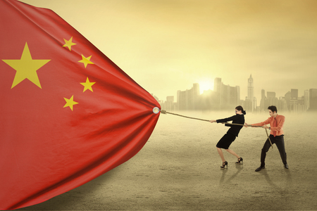 Young businesspeople pulling a chinese flag together, shot outdoors