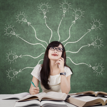 Image of a smart college student studying in the classroom and thinks idea with a branchy light bulb on the blackboard