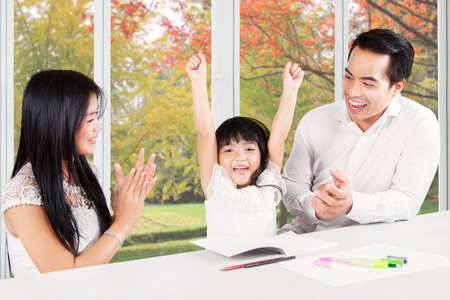 applause: Image of two young hispanic parents giving applause on their child at home after finishing homework