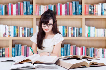 learning by doing: Image of a lovely female student with long hair sitting in the library while learning and doing school task
