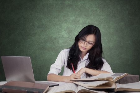 indian youth: Photo of a pretty female learner with long hair, studying in the class and write on the book with a laptop on the table Stock Photo