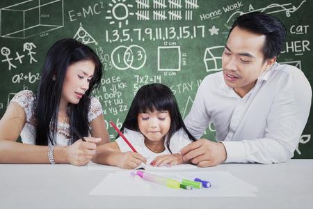 mom dad: Imagen de una niña que hace la tarea escolar y escribir en el libro en el salón de clase con dos profesores Foto de archivo