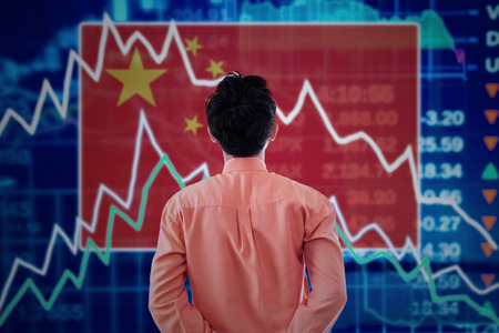 crisis economica: Corredor masculino joven que mira un mercado de valores de China con la disminución de las flechas