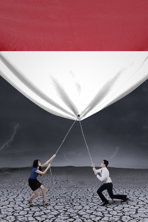 finance concept: Young asian businesspeople bring down a big indonesian flag, shot outdoors Stock Photo