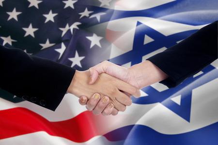 buen trato: Dos hombres de negocios dándose la mano después de mucho frente a los de las banderas americanas y israel