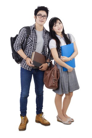 attitudes: Full length portrait of two high school student with trendy clothes, standing in the studio, isolated on white background