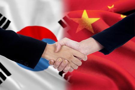 buen trato: Dos pol�ticos d�ndose la mano despu�s de mucho frente a las banderas chinos y surcoreanos