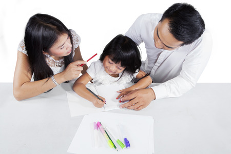 father teaching daughter: Unique perspective of two young parents  teaching their child to learn and doing homework Stock Photo