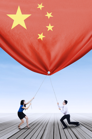 Young businesswoman with her partner pulling down a chinese flag, shot outdoors 版權商用圖片