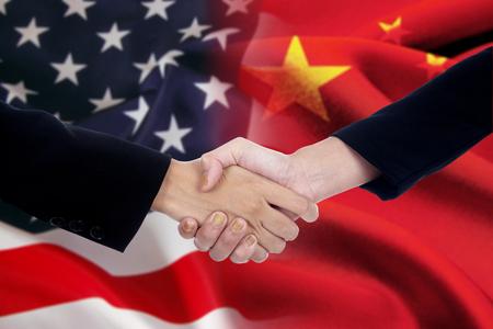 buen trato: Dos hombres de negocios apretón de manos después de mucho delante de una bandera americana y china