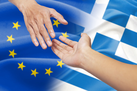 rescuing: Hand rescuing a person by pulling the hand in front of the europe and greece flag