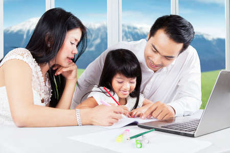 teaching: Photo of a cheerful little girl doing homework with her parents and try to write on the book, shot at home