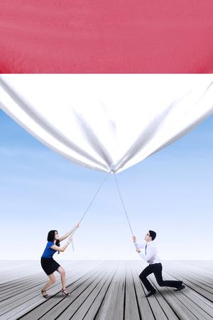 jonge ondernemers: Twee jonge ondernemers naar beneden trekken van een grote Indonesische vlag, buiten schot