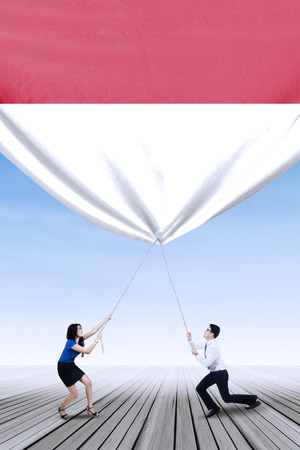 the indonesian flag: Two young entrepreneurs pulling down a big indonesian flag, shot outdoors