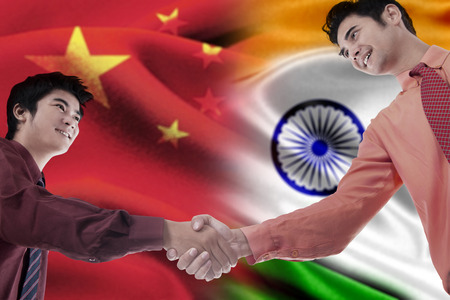 indonesian flag: Young chinese person shaking hands with indian person in front of the chinese and indian flags Stock Photo