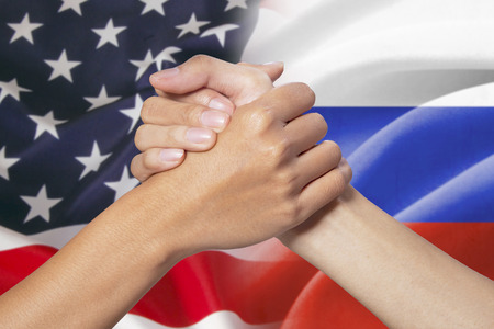 american flags: Two hands with partnership hands poses in front of the american and russian flags