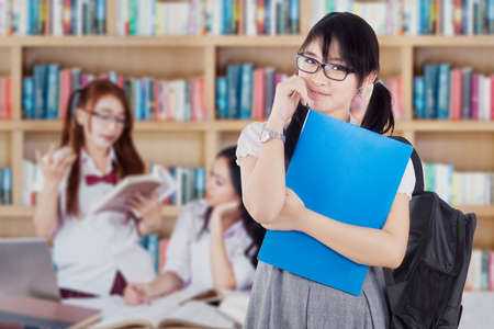 youth group: Image of a beautiful female student standing in the library with her group studying on the back