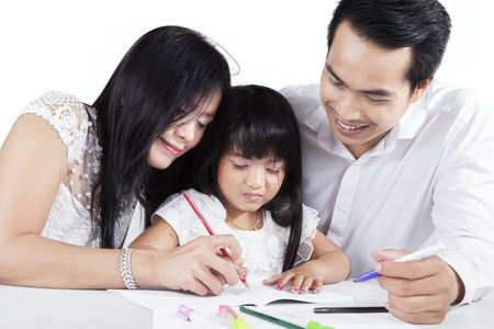 father teaching daughter: Portrait of happy asian family with two parents teaching their daughter to write on the book, isolated on white background