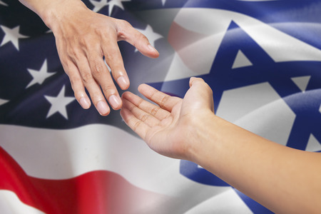 flag of israel: Hand pulling a person hand and giving a help in front of american and israel flags