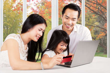 kid portrait: Cheerful parents and their daughter using laptop and credit card for shopping online at home with autumn background on the window