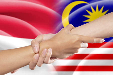 grabbing: Hand grabbing a person hand for helping in front of the indonesian and malaysian flags Stock Photo