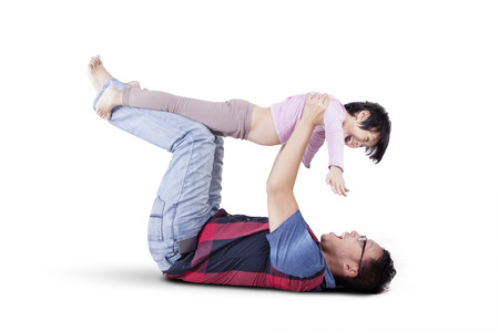 white playful: Playful father lifting his daughter in the studio, isolated on white background